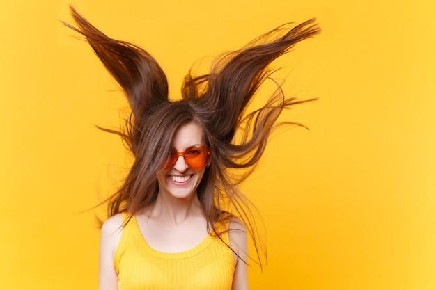 Portret van opgewonden vrolijk gelach grappige komische vrouw in oranje bril met fladderende haar kopie ruimte geïsoleerd op gele achtergrond. mensen oprechte emoties, lifestyle concept. reclame gebied.