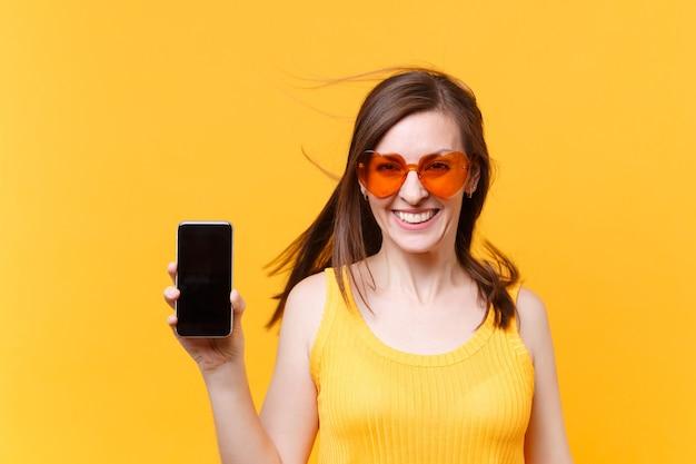 Portret van opgewonden vrolijk lachen grappige komische vrouw in oranje bril met fladderende haren houd mobiele telefoon met lege lege scherm kopie ruimte geïsoleerd op gele achtergrond. reclame gebied.