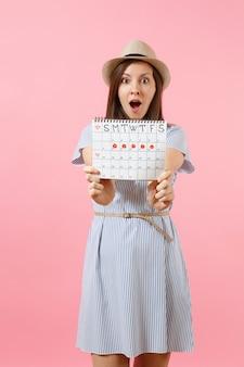 Portret van opgewonden vrouw in blauwe jurk, hoed met periodenkalender voor het controleren van menstruatiedagen geïsoleerd op heldere trending roze achtergrond. medisch, gezondheidszorg, gynaecologisch concept. ruimte kopiëren