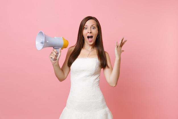 Portret van opgewonden vrouw met geopende mond in witte jurk met megafoon, handen uitspreidend