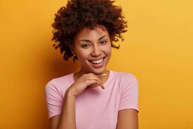 Portret van optimistisch vriendelijk ogende vrouw houdt hand onder de kin