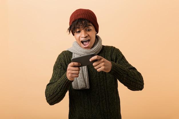 Portret van optimistische afro-amerikaanse gamerjongen die hoed en sjaal draagt die videospelletjes op smartphone speelt, die over gele muur wordt geïsoleerd