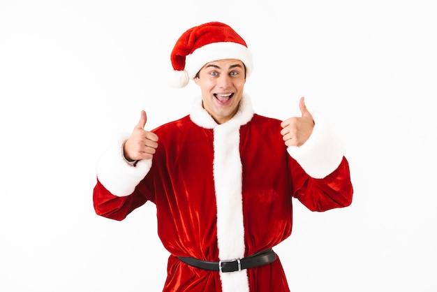 Portret van optimistische man 30s in kerstman kostuum en rode hoed gebaren met glimlach