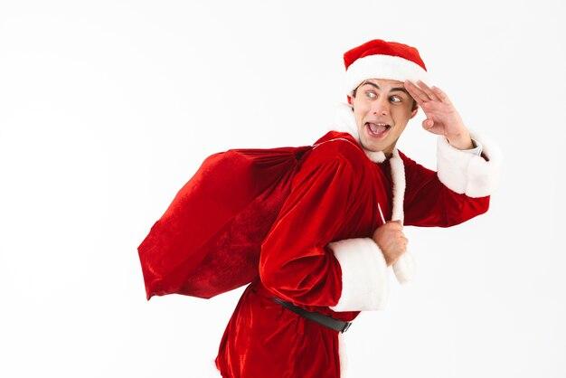 Portret van optimistische man 30s in kostuum van de kerstman en rode hoed met cadeauzakje over schouder