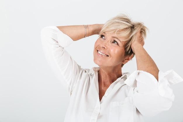 Portret van optimistische volwassen vrouw met kort blond haar die haar hoofd grijpt en lacht om copyspace geïsoleerd over witte muur in studio