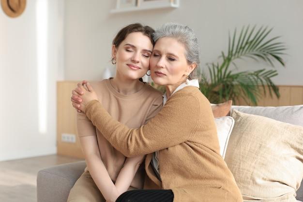 Portret van oude moeder en volwassen dochter die thuis knuffelen. gelukkig senior moeder en volwassen dochter omarmen met liefde op de bank.