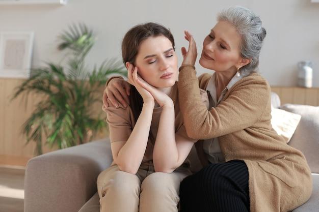 Portret van oude moeder en volwassen dochter die thuis knuffelen. gelukkige vertrouwde relaties. familieconcept.