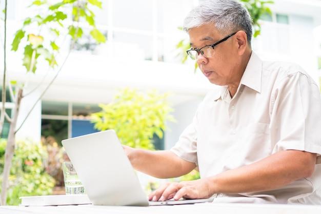 Portret van oude oudere aziatische man met behulp van een computer laptop