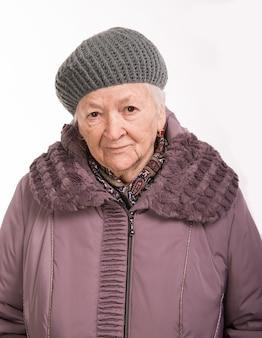 Portret van oude vrouw in winteruitloper op witte achtergrond