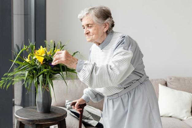 Portret van oudere grootmoeder aanraken van bloemen