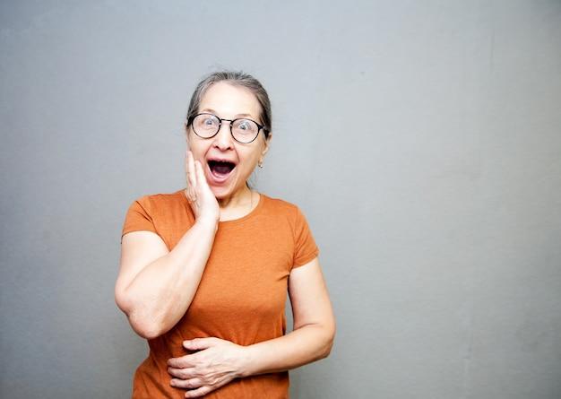 Portret van oudere verraste vrouw die haar mond opende