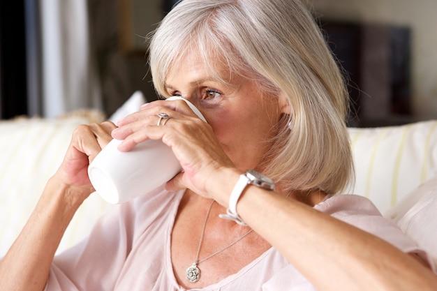 Portret van oudere vrouw het drinken van thee op de bank binnenshuis