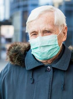 Portret van oudere vrouw in de stad die medisch masker draagt