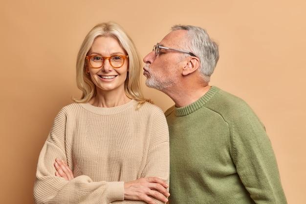 Portret van oudere vrouw krijgt aanhankelijke kus van echtgenoot hebben goede relatie gekleed op casual truien geïsoleerd over bruine muur