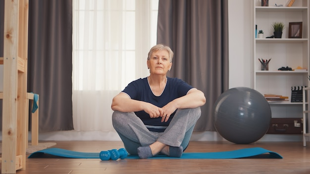 Portret van oudere vrouw zittend op yogamat. actieve oude vrouw trainen en een gezonde levensstijl uitoefenen in een gezellig appartement