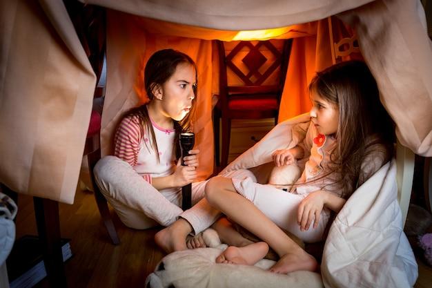 Portret van oudere zus die laat in de nacht in de slaapkamer een eng verhaal vertelt aan jongere younger