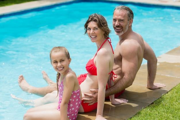 Portret van ouders en dochter zittend op zwembad in zwembadwater