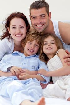 Portret van ouders en kinderen die in bed liggen