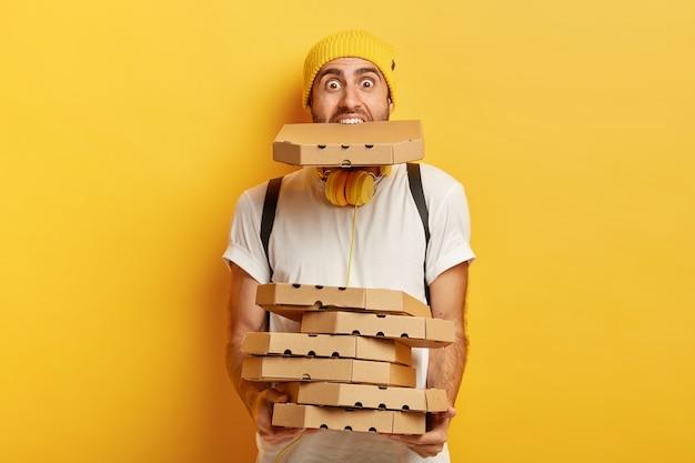 Portret van overbelaste pizza man houdt veel kartonnen verpakkingen, een in de mond, draagt casual wit t-shirt.