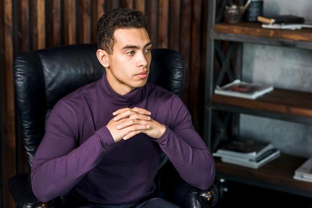 Portret van overweegt jonge man draagt paarse polo nek zittend op fauteuil wegkijken