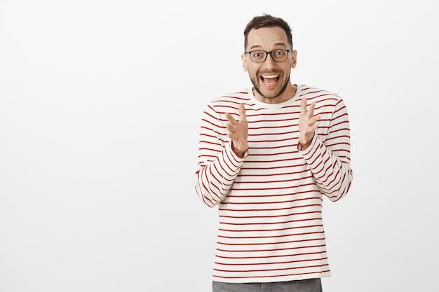 Portret van overweldigd schattige europese man met varkenshaar in trendy zwarte bril, handpalmen schudden terwijl iets geweldigs uitleggen