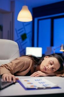 Portret van overwerkte zakenvrouw slaapbureau in hoofdkantoor. werknemer valt in slaap terwijl hij 's avonds laat alleen op kantoor werkt voor een belangrijk bedrijfsproject.