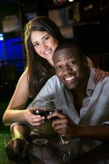 Portret van paar die en hun wijnglazen glimlachen roosteren bij barteller in bar