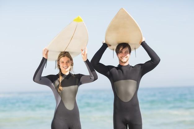 Portret van paar in wetsuit dragende surfplank lucht