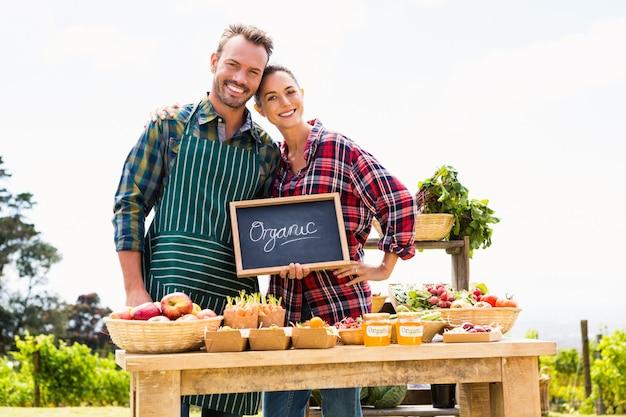 Portret van paar met bord dat organische groenten verkoopt