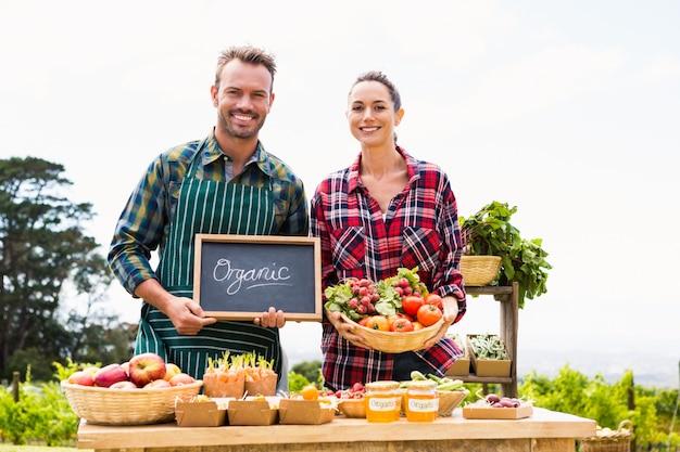 Portret van paar met bord en mand verkopende groenten