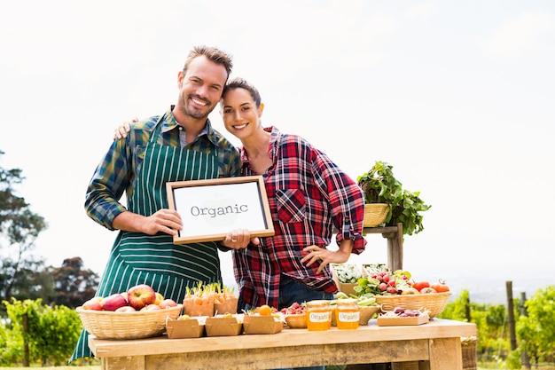 Portret van paar met leeg bord die organische groenten verkopen