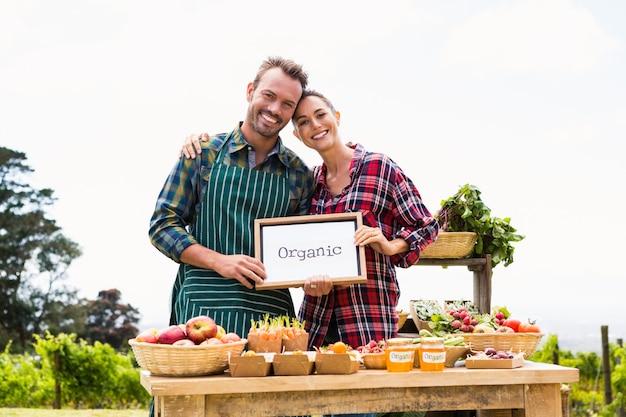 Portret van paar met lege bord verkopende groenten