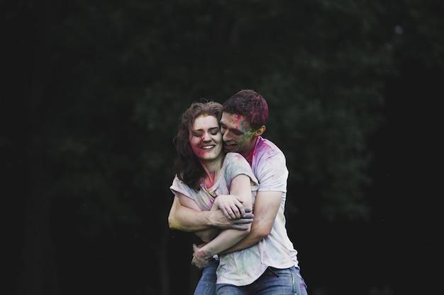 Portret van paar verliefd knuffelen op holi-kleurenfestival