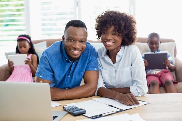 Portret van paar zitten met rekeningen en rekenmachine op tafel