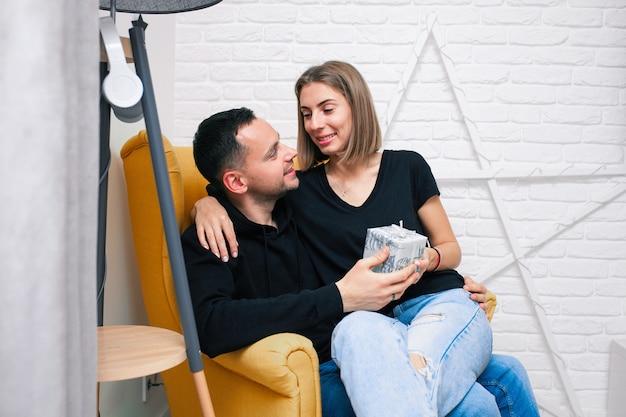 Portret van paarjongelui in een comfortabele ruimte. een man zit op een gele stoel. een vrouw zit op de schoot van een man en houdt een cadeau kerstvakantie met het gezin. modern interieur.