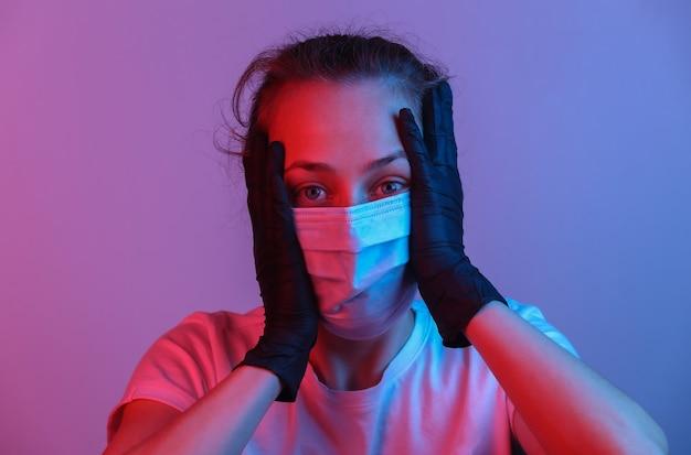 Portret van paniekvrouw met een medisch masker. roze blauw gradiënt neonlicht. pandemische bescherming covid-19