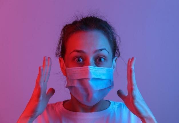 Portret van paniekvrouw met een medisch masker. roze blauw gradiënt neonlicht
