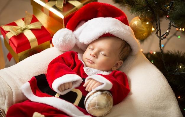 Portret van pasgeboren babyjongen in kerstmankleren die onder de kerstboom liggen