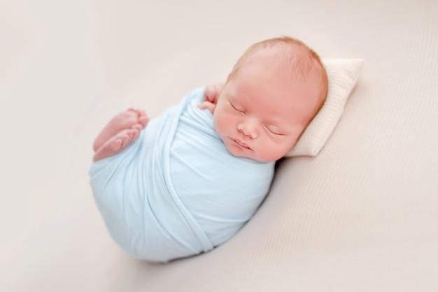 Portret van pasgeboren babyjongen ingebakerd in lichtblauwe stof die op een witte achtergrond slaapt en kleine voetjes omhoog houdt. schattig baby kind aan het dutten tijdens studio fotoshoot