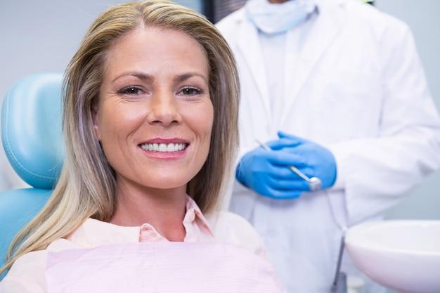 Portret van patiënt zittend op een stoel tegen tandarts