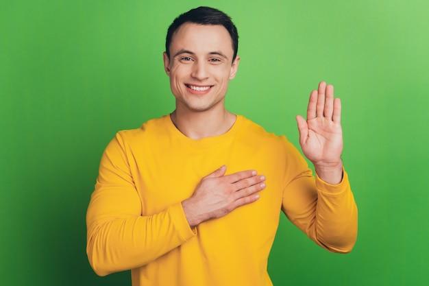 Portret van patriot man handen borst verhogen palm maken gelofte op groene achtergrond