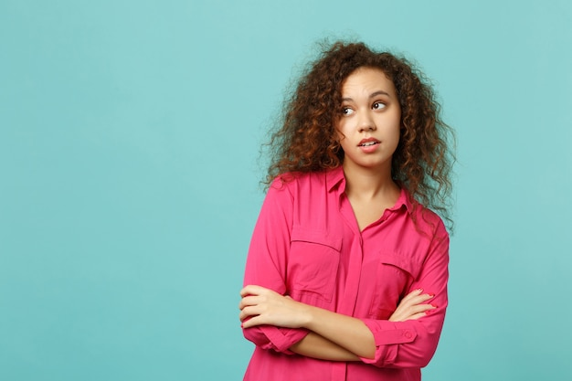 Portret van peinzend afrikaans meisje in roze casual kleding opzij kijken, hand in hand gekruist geïsoleerd op blauwe turquoise muur achtergrond. mensen oprechte emoties, lifestyle concept. bespotten kopie ruimte.