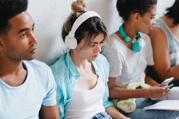 Portret van peinzend meisje met trendy kapsel, zittend tussen vrienden en luisteren muziek in grote witte koptelefoon. jonge dame in blauw shirt neerkijkt genieten van favoriete liedje.