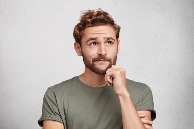 Portret van peinzende aangenaam ogende jonge man met baard en snor, houdt hand onder de kin