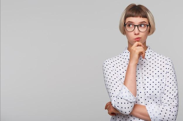 Portret van peinzende aantrekkelijke blonde jonge vrouw draagt polka dot shirt