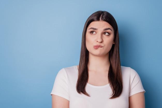 Portret van peinzende doordachte dromerige dame bijt lip kijk lege lege ruimte op blauwe achtergrond