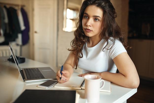 Portret van peinzende doordachte student meisje studeren vanuit huis, zittend op haar werkplek voor opengeklapte laptop