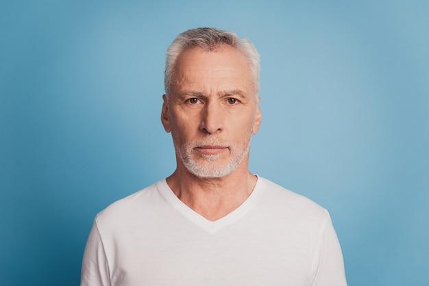 Portret van peinzende ernstige met witte haren oude man geïsoleerd op blauwe achtergrond