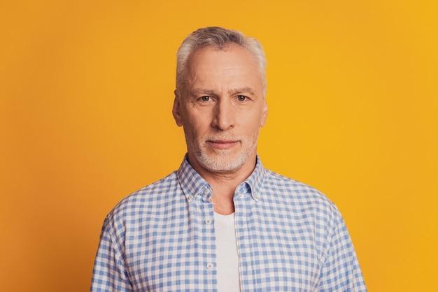 Portret van peinzende ernstige met witte haren oude man geïsoleerd op gele achtergrond