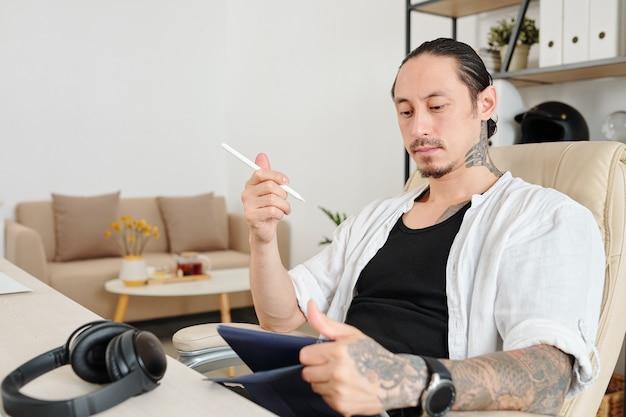 Portret van peinzende grafisch ontwerper met stylus en tafelcomputer in handen die aan bedrijfslogo werken